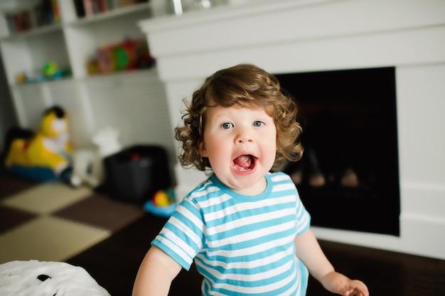 아름다운 곱슬머리 소년이 입을 벌리고 이빨을 보여줍니다