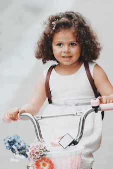 Beautiful curly little girl riding a bicycle with a basket of flowers. high quality photo
