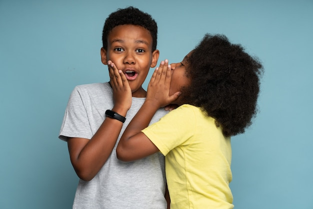 Beautiful curly little girl in yellow t shirt telling secret to her lovely brother