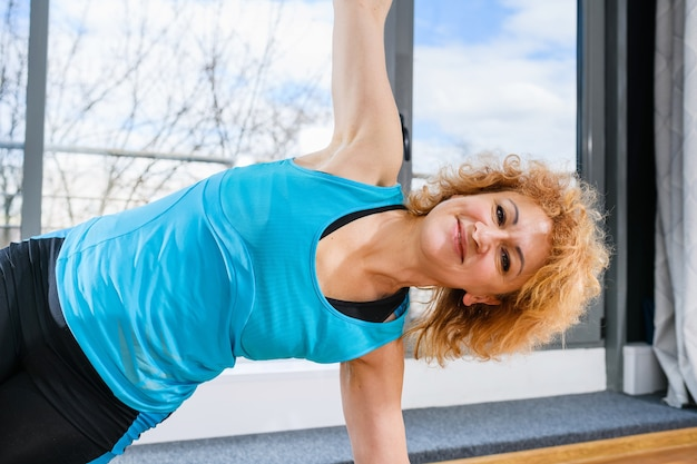 Beautiful curly middle age fit woman doing side yoga fitness plank with wide hands, happy face