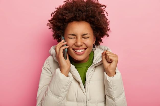美しい巻き毛の女性は、現代のスマートフォンを介して友人を呼び出し、くいしばられた握りこぶしを上げ、広く笑顔で、フード付きの白いジャケットを着て、ピンクの背景のモデル。
