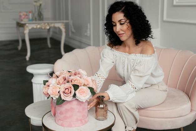 ピンクのソファに座って、ベルベットの箱のピンクの花に触れる美しい巻き毛の女性