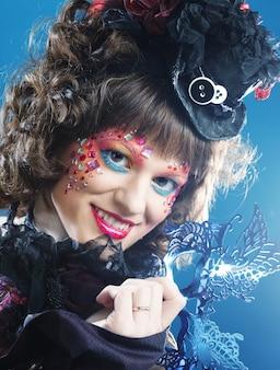 マスクを持つ美しい巻き毛の女性。カーニバルの顔。休日の写真。
