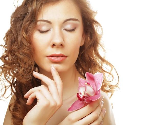 Красивая кудрявая женщина с розовой орхидеей