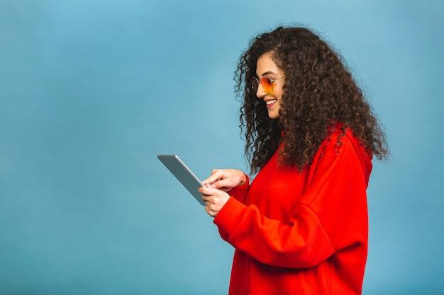 赤い背景の上に分離されたタブレットを使用して笑っている美しい巻き毛の少女。スペースをコピーします。