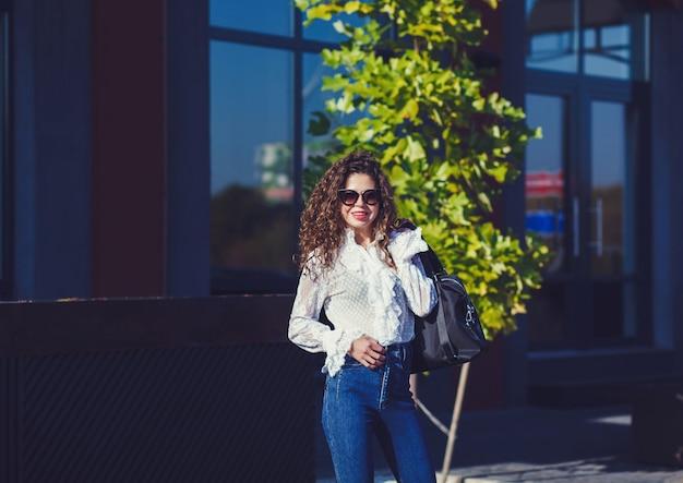 Красивая курчавая молодая женщина в солнечных очках