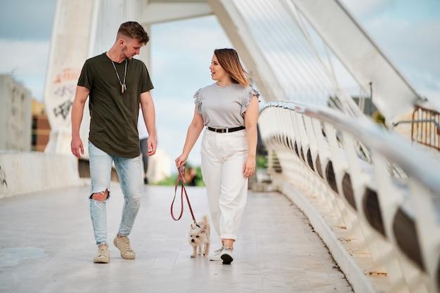 美しい曲線モデルとハンサムな男が都会のシーンで犬と一緒に散歩