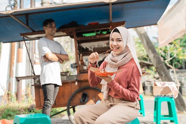 通りの売り手から食べ物を注文する美しい顧客