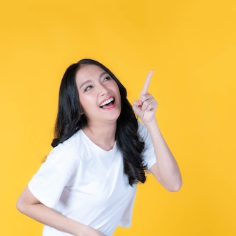 Beautiful cute asian woman smiling and pointing finger to empty copy space , blank space for advertising isolated on yellow background