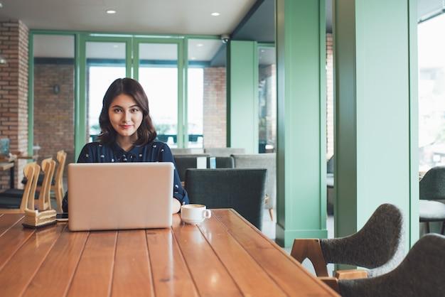 Красивая милая азиатская молодая коммерсантка в кафе, используя ноутбук и пить кофе улыбается