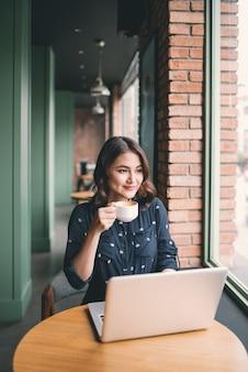 Красивая милая азиатская молодая женщина в кафе, наслаждается питьевой улыбкой кофе