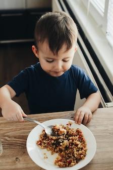 美しいかわいい赤ちゃんは、キッチンでスプーンでご飯を食べます