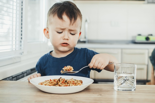 Beautiful cute baby eats rice with a spoon in the kitchen