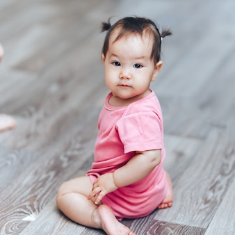 Beautiful cute baby kazakh one year old girl sittimg on floor at home