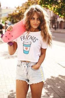 거리 배경에 핑크 페니 스케이트 보드 포즈 여름 힙 스터 흰색 옷을 입고 메이크업없이 아름 다운 귀여운 금발 십 대 모델