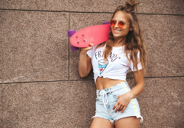 Beautiful cute blond teenager model without makeup in summer hipster white clothes with pink penny skateboard posing near wall on the street