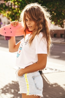 Beautiful cute blond teenager model without makeup in summer hipster white clothes with pink penny skateboard posing on the street background