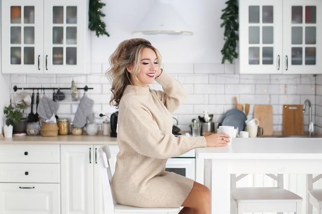 明るい装飾が施されたキッチンで朝食をとっているホームドレスの美しいかわいいブロンドの女性