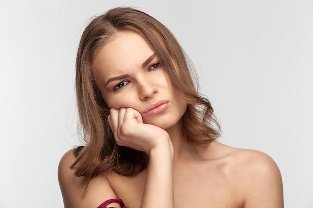 Красивая милая брюнетка девушка с недовольным лицом