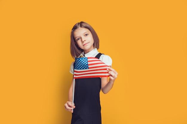 아름다운 백인 여학생은 노란 배경 미국 국기에 미국 국기를 들고 있다