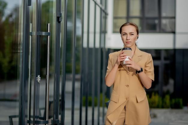아름 다운 귀여운 백인 젊은 사업가 커피 컵, 휴대 전화를 사용 하 고 마시는 커피 웃 고.