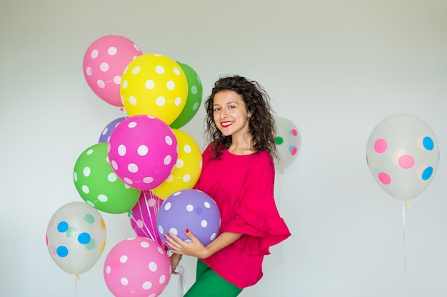 Beautiful cute cheerful girl with colored balloons. holiday happy birthday.