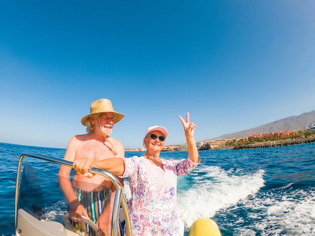 Beautiful and cute couple of seniors or old people in the middle of the sea driving and discovering new places with small boat. mature woman holding a phone and taking a selfie with hew husband