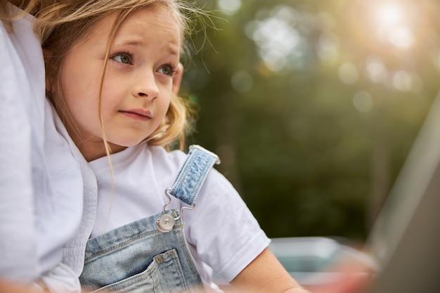 공원에서 어머니와 함께 쉬고 흰 셔츠에 아름 다운 귀여운 여자 아이