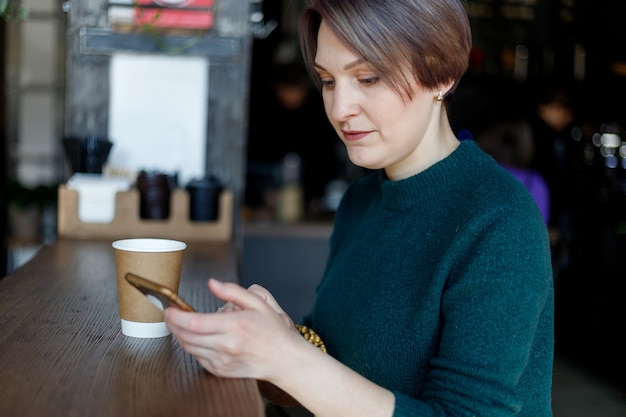 Beautiful cute girl in the cafe looking at the camera with coffee smiling. green knitted sweater. fashionably dressed girl. girl looks at the phone. business lady