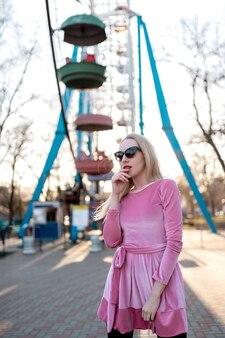 Красивая милая девушка в розовом платье гуляет в парке развлечений