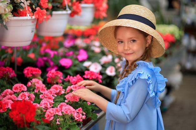 Красивая милая девушка в соломенной шляпе в оранжерее с яркими цветами