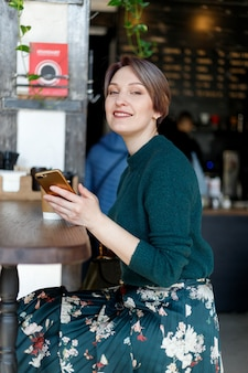 커피 미소와 함께 카메라를 보고 카페에서 아름 다운 귀여운 소녀. 녹색 니트 스웨터. 세련되게 옷을 입은 소녀. 소녀는 전화를 찾습니다. 비즈니스 레이디