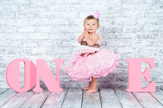 Beautiful and cute girl in a pink dress with the letters one on her first birthday. emotional girl.