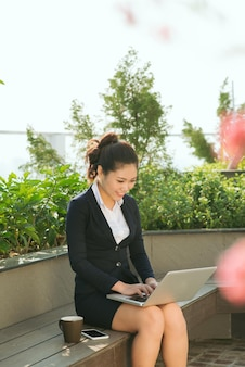Красивая милая девушка улыбается в одежде деловой женщины, используя портативный компьютер в парке