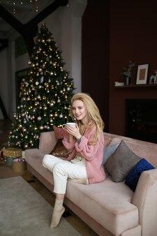 マグカップを持つ美しいかわいい女の子は、自宅の木の近くのソファに座ってコーヒーを飲んでいます