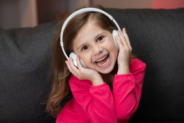 Beautiful cute happy little girl listens to music on wireless headphones. funny little girl dancing, singing and moving to rhythm. kid wearing headphones.