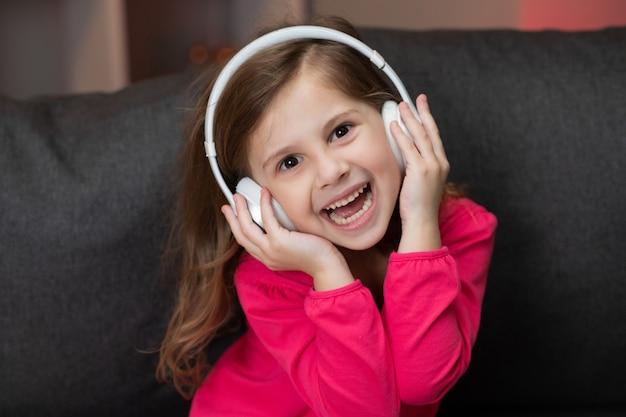 아름 다운 귀여운 행복 소녀 무선 헤드폰에서 음악을 수신합니다. 춤, 노래 및 리듬으로 이동 재미있는 작은 소녀. 헤드폰을 착용하는 아이.