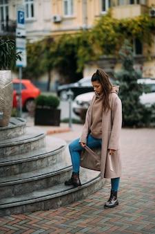 Bella donna castana sorridente felice sveglia che cammina intorno alla città