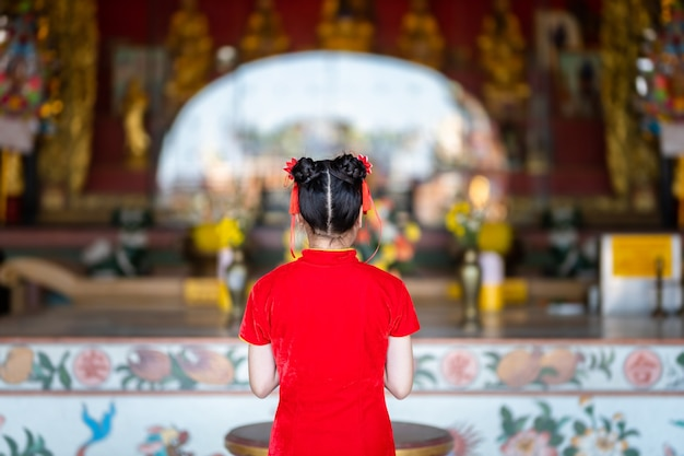 Beautiful cute little asian young woman wearing red traditional chinese cheongsam, stand for pray to buddha statue for chinese new year festival at chinese shrine
