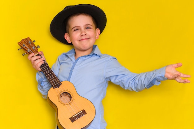 Beautiful cute little boy in hat and shirt keeps guitar isolated on yellow
