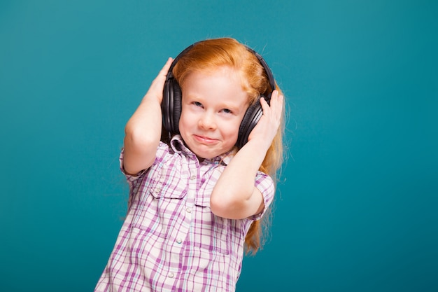 Beautiful, cute little girl in checkered shirt and earphones with long red hair listen to musik
