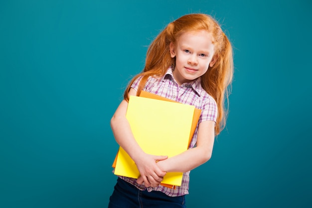Beautiful, cute little girl in checkered shirt with long red hair cares papers