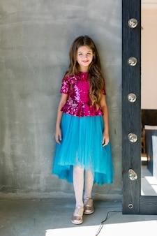 Красивая милая маленькая девочка в розовой сияющей блузке и синей юбке на сером фоне, стоящем около зеркала.