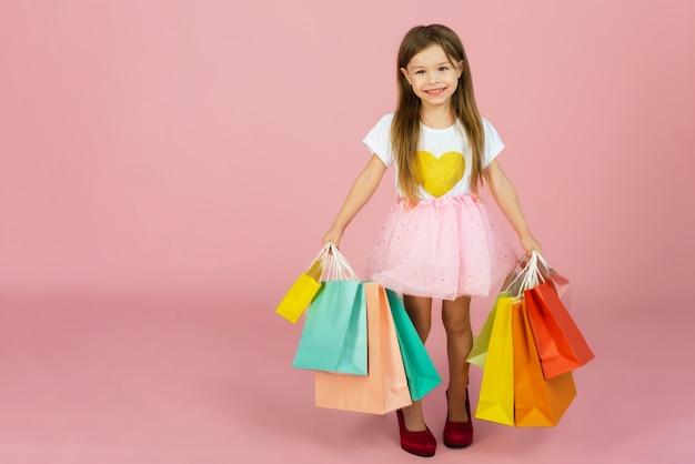 長いブロンドの髪を持つ美しいかわいい女の子、ピンクの壁に分離されたカラフルなパッケージと母親の大きな靴に立っているチュールスカート。