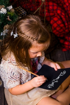 Beautiful cute little girl writes letter to santa near christmas decoration on the wooden floor