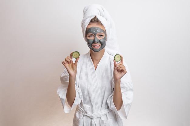 클레이 마스크와 함께 오이를 들고 그녀의 머리에 목욕 가운과 수건 포즈 아름다운 귀여운 모델