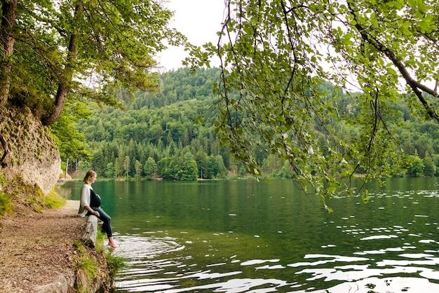 森の中の山の湖の近くの美しく、かわいい妊婦。