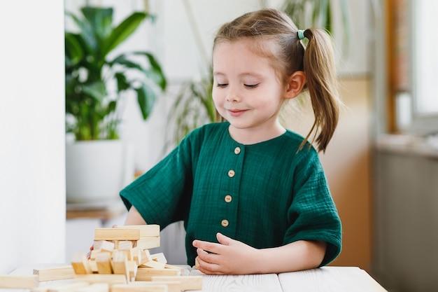 아름다운 귀여운 미취학 아동은 집에서 탁자 위에 나무 블록을 가지고 노는 자연적인 촉각 발달