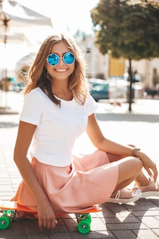 Beautiful cute smiling blond teenager model in summer hipster clothes sitting on orange penny skateboard . positive woman