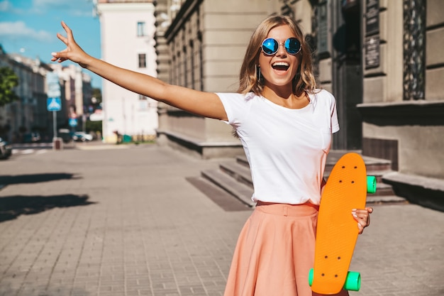 Beautiful cute smiling blond teenager model in summer hipster clothes with orange penny skateboard posing . showing peace sign